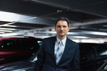 Handsome, attractive young happy, smiling, businessman closeup face portrait standing in indoors parking lot in suit and tie on interview break