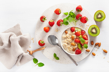 healthy breakfast with oatmeal porridge, strawberry, nuts. Top view