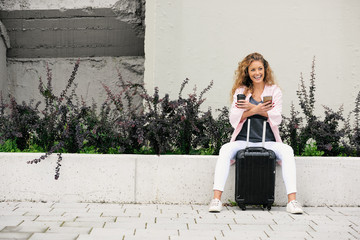 Female traveler using smart phone and holding coffee while sitting on the wall. Luggage next to her.