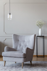 Light beige, elegant armchair and a black vase stand in a sophisticated living room interior with molding on beige walls