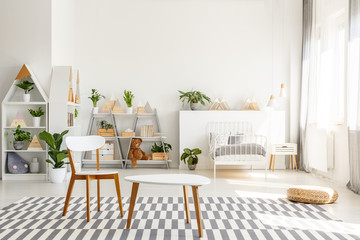 White wooden chair and table set, green plants in a spacious, sunlit teenager bedroom interior with scandinavian decor