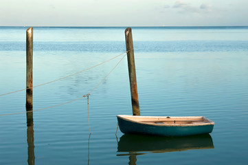 Solitary small boat moored at soft blue sunrise in the Florida Keys