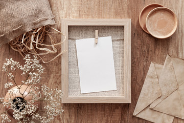 Wooden autumn desk with dried decoration, vase with white flowers, old envelopes, ceramic and mockup frame