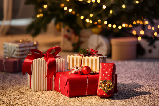 Beautiful Christmas gift boxes on floor near fir tree in room