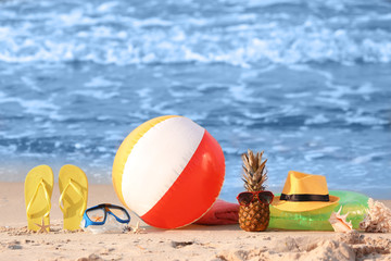 Pineapple with sunglasses and beach items on sand near sea
