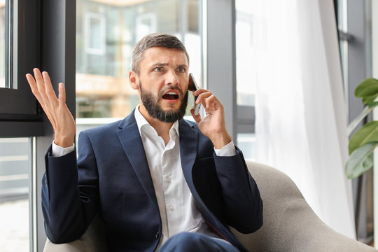 Emotional businessman talking on phone in office