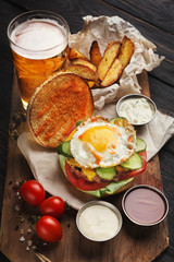 Hamburger with bacon and egg on wooden platter