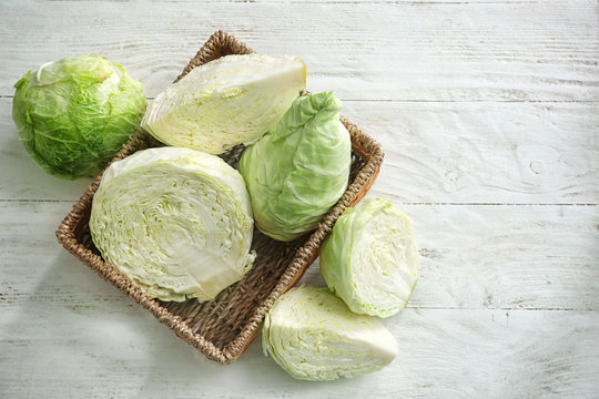 Wicker basket with fresh cabbage on white table