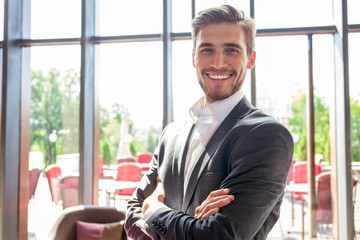 Portrait of happy businessman with arms crossed standing in office.