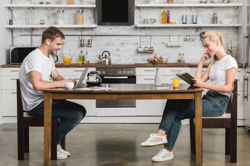 side view of happy young couple reading book and using laptop while having breakfast at kitchen table