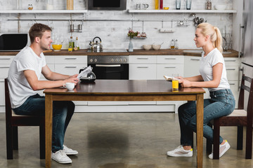 side view of young couple reading and looking at each other while having breakfast together