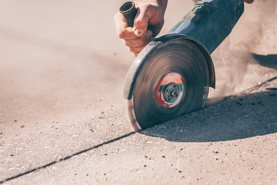 A close-up of a working angle grinder with a diamond disc