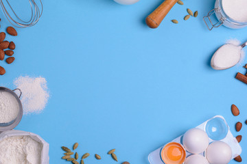 Baking ingredients for homemade pastry on blue background. Bake sweet cake dessert concept. Top view. Flat lay. Copy space