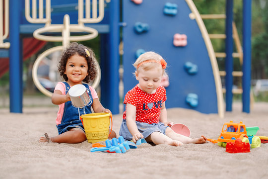 Happy childhood. Two cute Caucasian and hispanic latin babies children sitting in sandbox playing with plastic colorful toys. Little girls friends having fun together on playground.