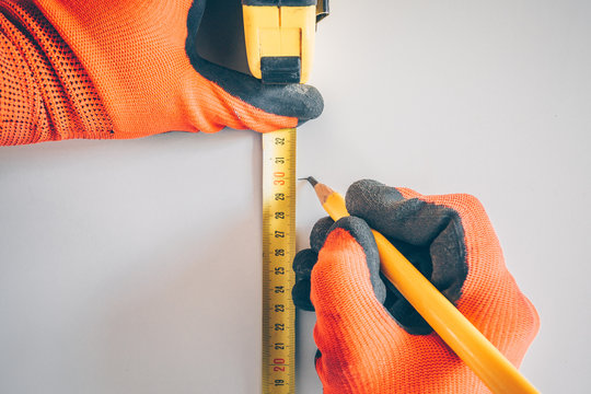First person view: a worker wearing gloves puts a mark on a white wall using a tape measure and a pencil