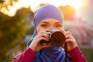Female photographer wearing a hijab. woman holding a camera hobbyist or a journalist in summer park autumn trees forest