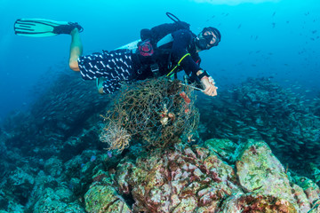 SCUBA diver removing an abandoned fishing net entangled on a tropical coral reef