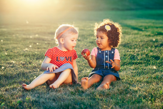Group portrait of white Caucasian and latin hispanic girls children sitting together sharing apple. Two babies eating fruits outside in park on summer day. Best friends forever. Healthy childhood.
