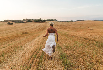 Young blond woman with white dress and short cut posing and walking by a dry straw countryside in a sunset of summer