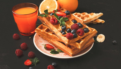 Belgian waffles with berries and fruits with juice glass