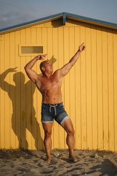 Muscular older man poses in yellow cabin background.