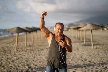 Elderly man listens to music on the beach.