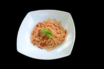 Spaghetti mit Tomatensoße und Basilikum vor schwarzem Hintergrund