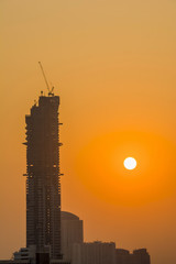 Wall Mural - View of construction building and crane during sunset.