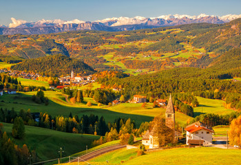 Incredible scenic view of traditional tyrol village with churches in alpine valley at autumn sunny day