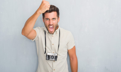 Handsome young man over grey grunge wall holding vintage photo camera annoyed and frustrated shouting with anger, crazy and yelling with raised hand, anger concept