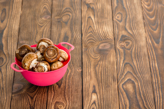 Small red bowl of fresh whole Baby Bella mushrooms