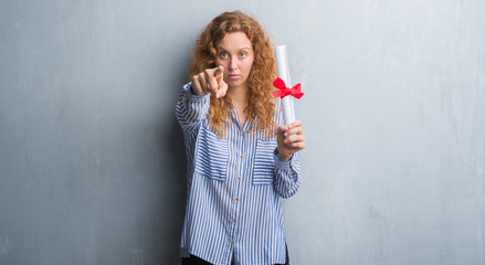Young redhead business woman over grey grunge wall holding diploma pointing with finger to the camera and to you, hand sign, positive and confident gesture from the front