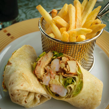 Plated shrimp and chicken wrap cut in half with french fries in small mesh wire basket. Hotel resort lunch/dinner meal menu.