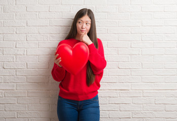 Young Chinese woman in love over brick wall holding red heart serious face thinking about question, very confused idea
