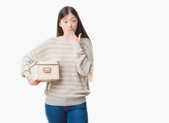 Young Chinese woman over isolated background holding a box cover mouth with hand shocked with shame for mistake, expression of fear, scared in silence, secret concept