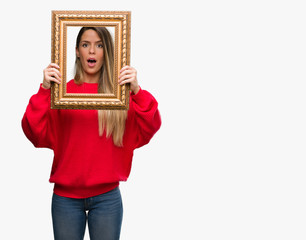 Beautiful young woman holding vintage frame scared in shock with a surprise face, afraid and excited with fear expression