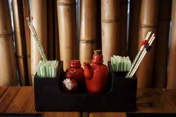 Sauce dish in a stand with napkins and chopsticks close-up against a background of bamboo.