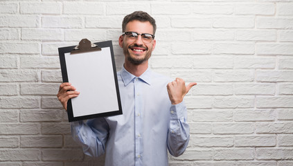 Young adult business man over brick wall holding clipboard pointing and showing with thumb up to the side with happy face smiling