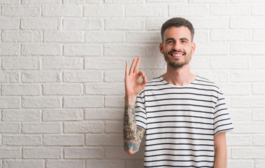 Young adult man standing over white brick wall doing ok sign with fingers, excellent symbol