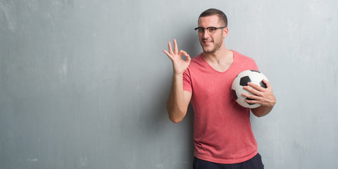 Young caucasian man over grey grunge wall holding soccer football ball doing ok sign with fingers, excellent symbol