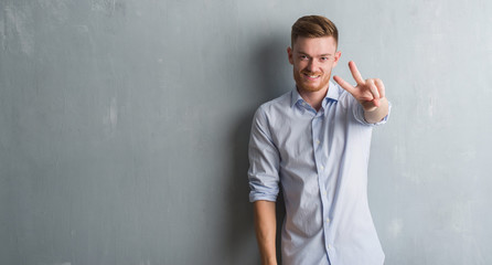 Young redhead business man over grey grunge wall smiling looking to the camera showing fingers doing victory sign. Number two.