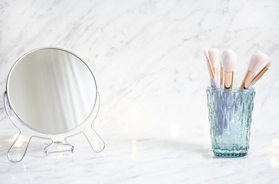 Feminine accessories on a marble dressing table.