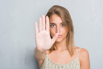 Beautiful young woman standing over grunge grey wall with open hand doing stop sign with serious and confident expression, defense gesture