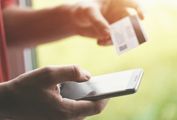 Hands holding credit card and using smartphone. Online shopping