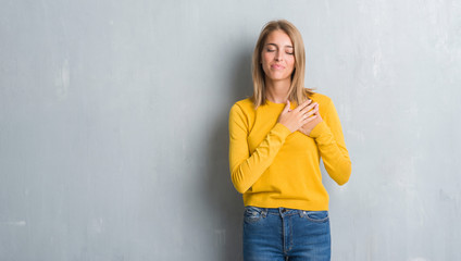 Beautiful young woman standing over grunge grey wall smiling with hands on chest with closed eyes and grateful gesture on face. Health concept.