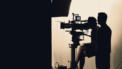 Video production behind the scenes which film crew team in silhouette shooting or recording tv movie commercial with professional equipment such as high definition 4k camera with monitor in studio