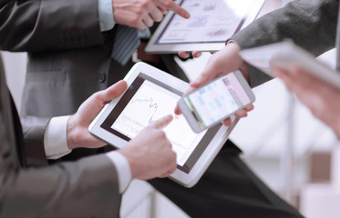 Businessmen at meeting presenting charts on smartphone, tablet