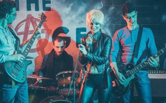 Sängerin und Rockband bei Gig auf der Bühne