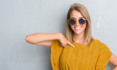 Beautiful young woman standing over grunge grey wall wearing retro sunglasses with surprise face pointing finger to himself