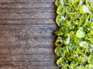 Olivine gemstone also called Peridot on old wooden background.Selective focus.
